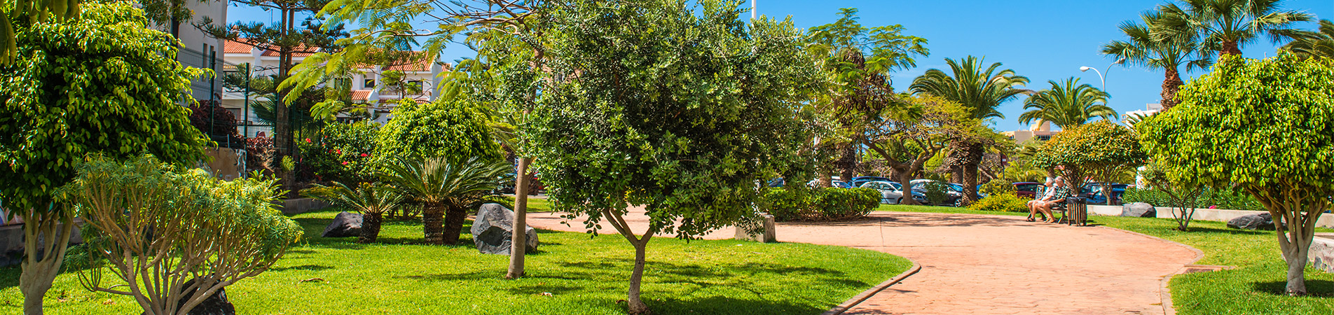 Pareja sentada en un banco del parque diseñado por inter jardinen el barranco aquilino en Los Cristianos, Arona