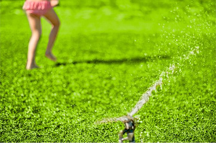 Niña corriendo sobre el cesped mojado con un aspersor de riego activando