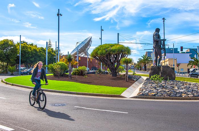 Chico montando en bicicleta junto al paisaje urbano de la rotonda del Museo de la Ciencia y el Cosmos en la Avenida de los Menceyes de San Cristobal de La Laguna