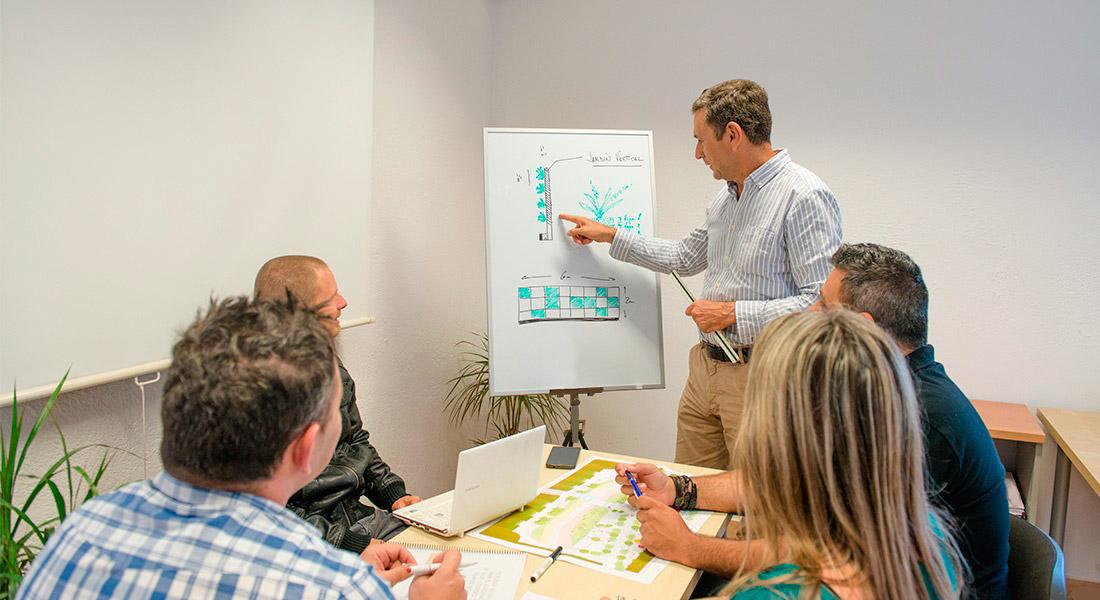 Augusto Guerra, tecnico agricola y genrente de Interjardín, explicando el diseño de un jardin verticala otros tecnicos en una reunion de trabajo