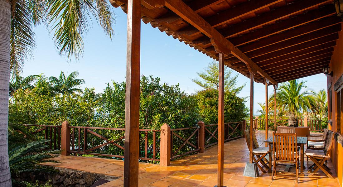 Vista del porche de una finca privada rodeada de un jardin diseñado por interjardin con plantas, palmeras y arboles frutales
