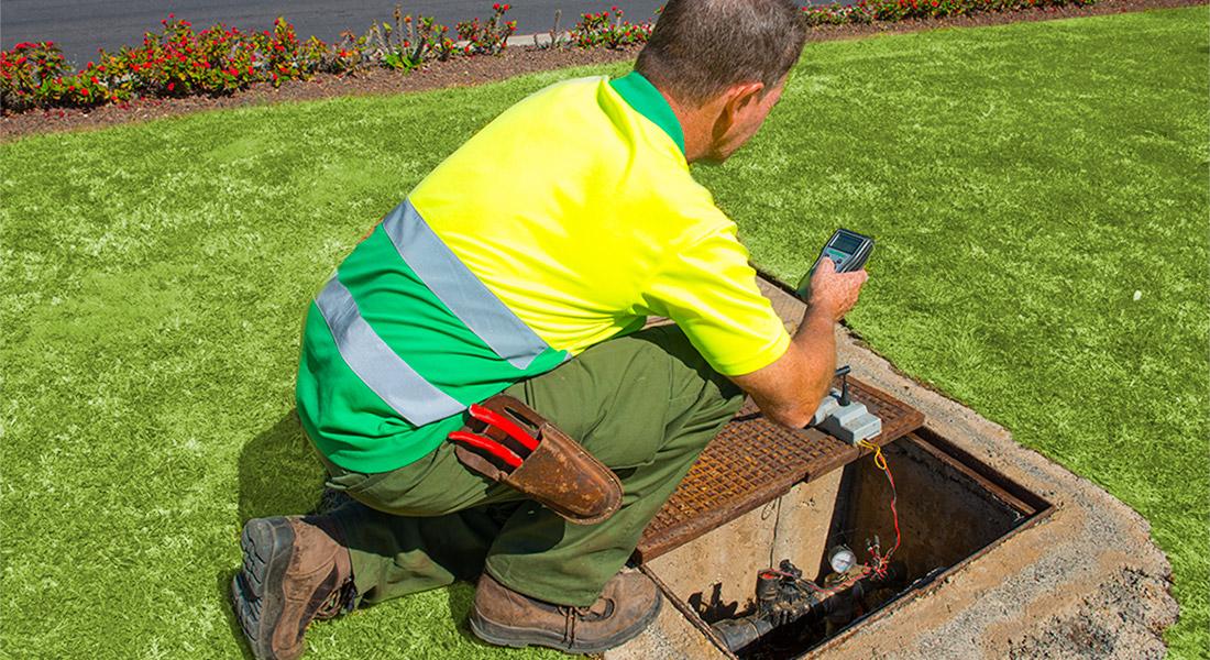 Trabajador de interjardin programando el riego por aspersion de un jardin público