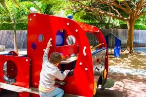 Niño jugando en mobiliario de parques infantiles con forma de camion en el parque Garcia Sanabria de Santa Cruz de Tenerife