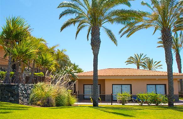 Jardin con cesped y palmeras de las villas del Hotel Dunas Paraiso en Los Cristianos, Arona