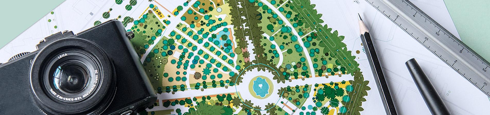 Detalle de una mesa de trabajo de inter jardin, donde se aprecia un fragmento de mapa del Parque Garcia Sanabria, una camara fotografica leica, un lapiz, un boligrafo y un escalimetro