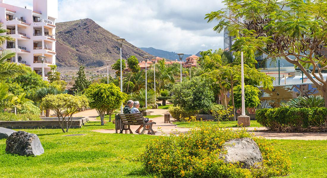 Pareja de ancianos sentada en un banco del parque diseñado por inter jardin en el barranco aquilino en Los Cristianos, Arona