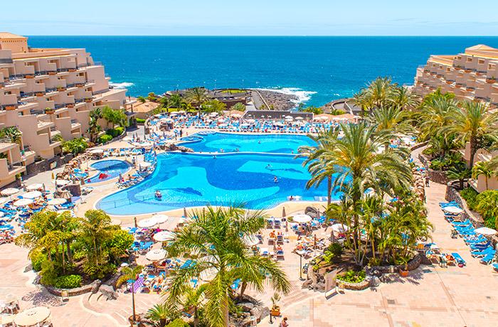 Vista de los jardines, palmeras y la piscina del Hotel Dunas Paraiso Los Cristianos Arona